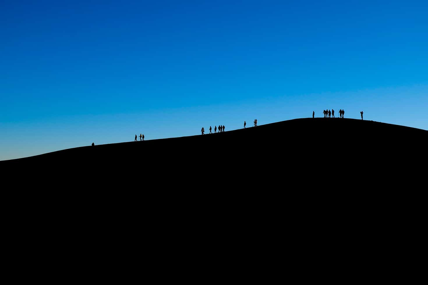 Hikers silhouetted while waiting for sunrise on Acatenango Volcano