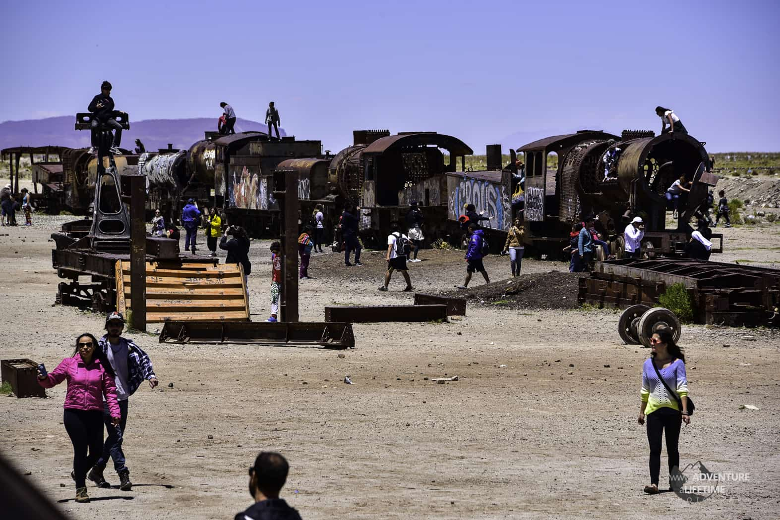 Tourists in Train Graveyard in Uyuni, Bolivia