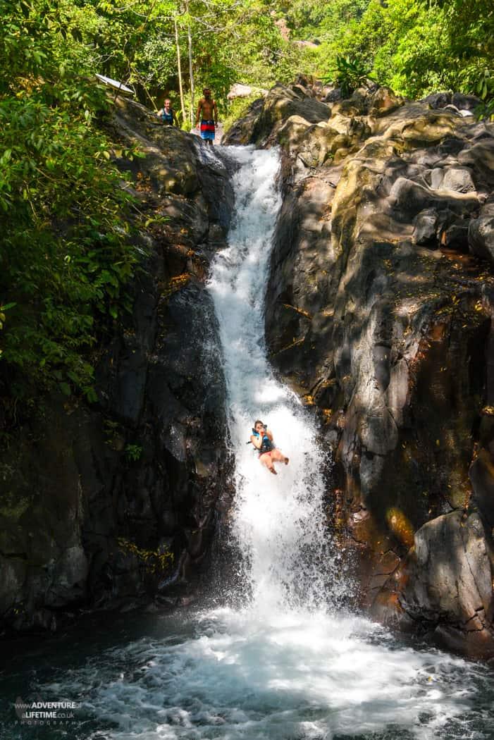 Nichole sliding down Aling Aling Waterfall, Bali