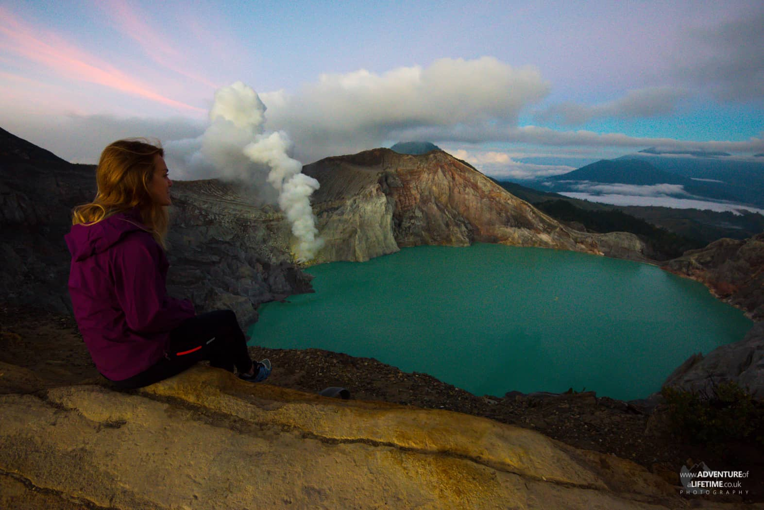 Dora sits on the crater of Ijen volcano looking down at the blue lake
